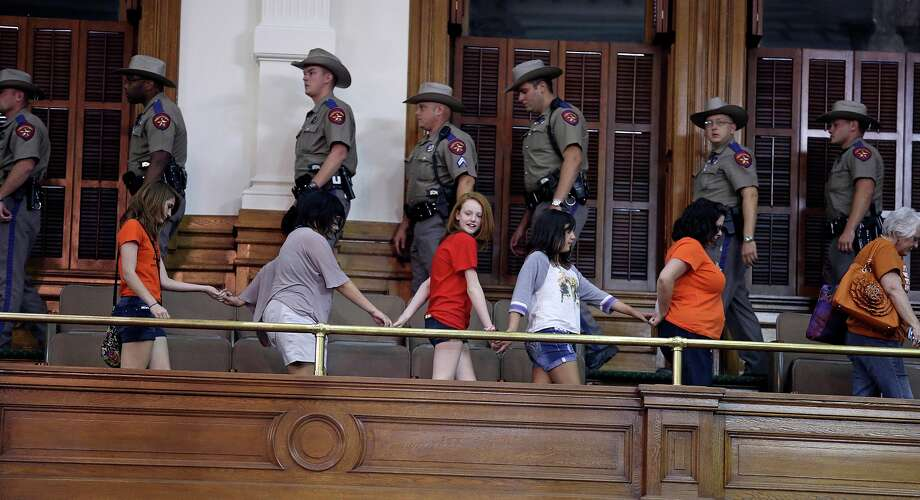 DPS Troopers march in as a line of supporters hold hands marching out after Fort Worth Senator Wendy Davis filibusters in an effort to cause abortion legislation to die without a vote on the floor of the Senate Tuesday, June 25, 2013. Photo: TOM REEL, San Antonio Express-News / San Antonio Express-News