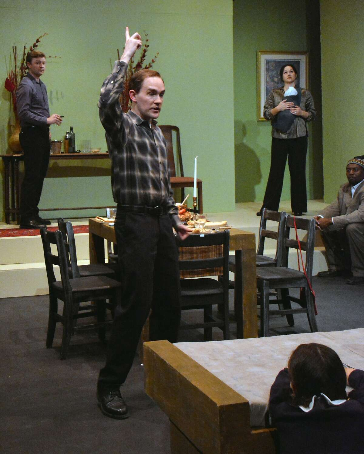"""Clay (Justin Gillman, center) tries to convince the rest of the family that some creature is gnawing at their avocados in Custom Made Theatre's """"The Pain and the Itch"""""""