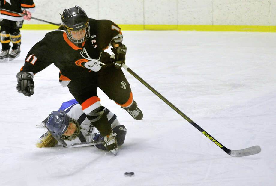 Darien's Sammy Nielsen falls to the ice trying to get the puck from Stamford/Westhill/Staples' Cassandra Miolene during their hockey game at Terry Conners Rink in Stamford, Conn., on Monday, Jan. 13, 2014. Darien won, 7-0. Photo: Jason Rearick / Stamford Advocate