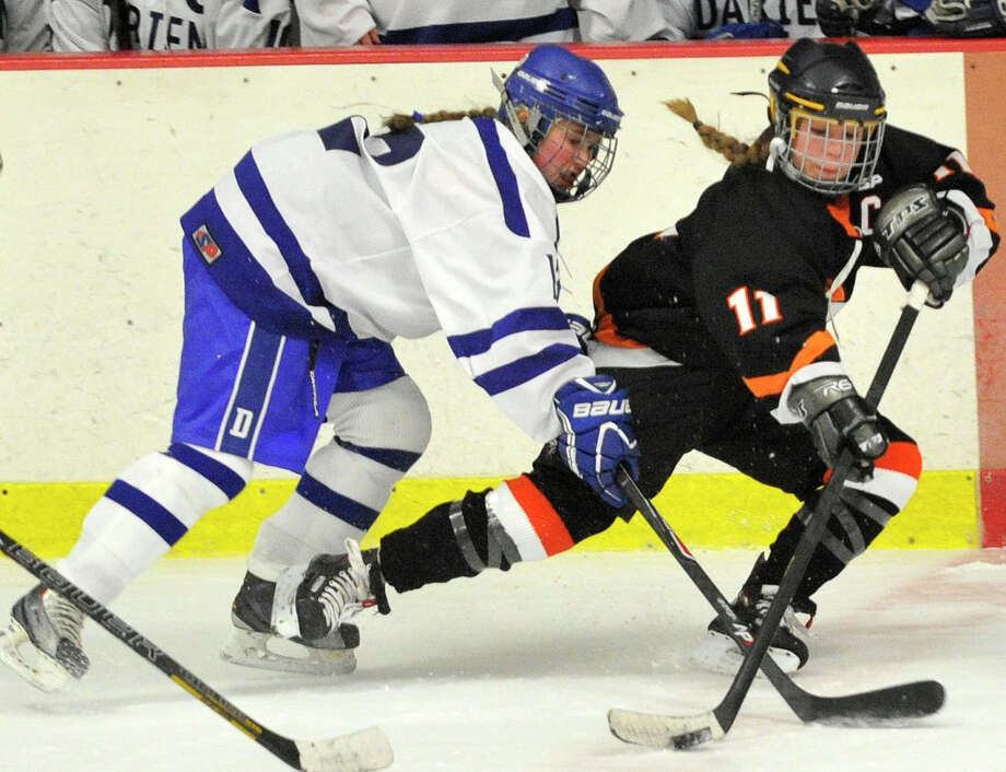 Stamford/Westhill/Staples' Cassandra Miolene brings the puck up the ice while under pressure from Darien's Amanda Sload during their hockey game at Terry Conners Rink in Stamford, Conn., on Monday, Jan. 13, 2014. Darien won, 7-0. Photo: Jason Rearick / Stamford Advocate