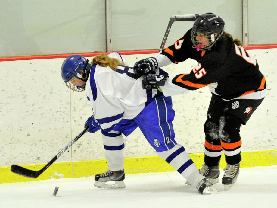 Darien's Hannah McLane keeps the puck from Stamford/Westhill/Staples' Kelly Guraian during their hockey game at Terry Conners Rink in Stamford, Conn., on Monday, Jan. 13, 2014. Darien won, 7-0. Photo: Jason Rearick / Stamford Advocate