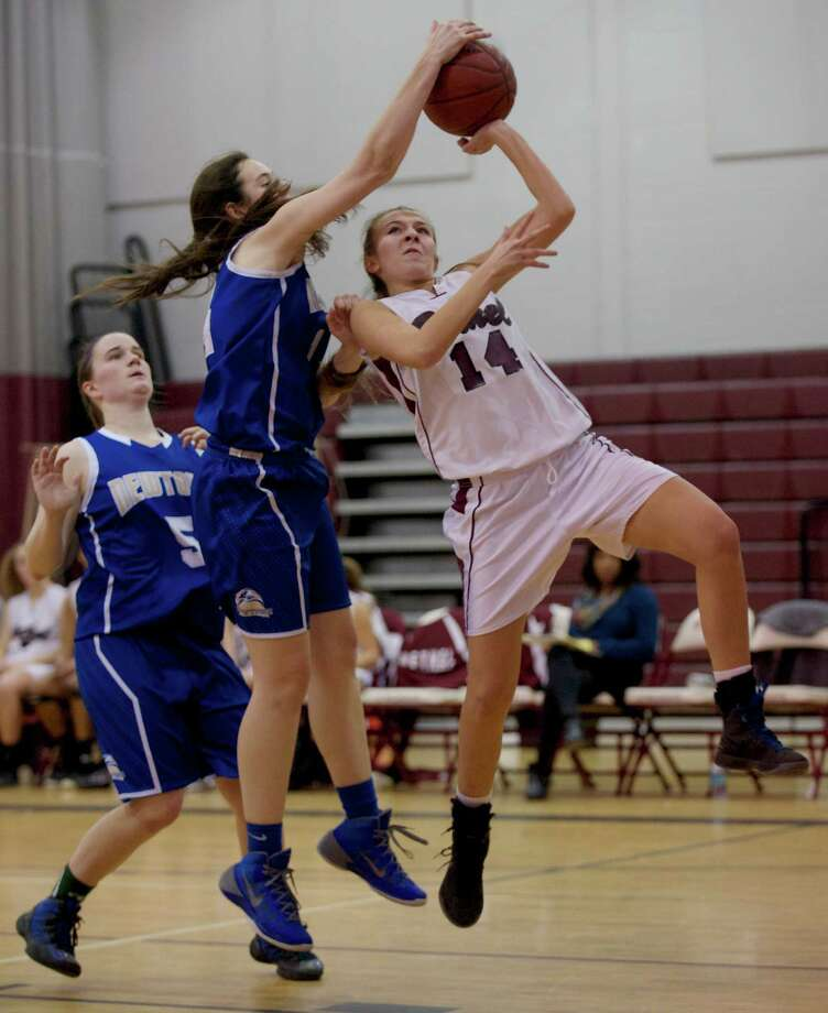 Newtown's Kelly Merrick (14) blocks a shot by Bethel's Kaelin Hogan (14) during the SWC girls basketball game between Newtown and Bethel, at Bethel High School, Bethel, Conn, on Thursday night, January 9, 2014. Merrick was called for a foul, behind them is Newtown's Cassie Ekstrom (5). Photo: H John Voorhees III / The News-Times Freelance