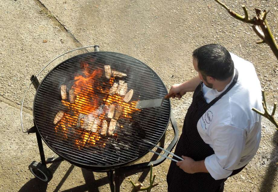 Dry Creek Kitchen chef Andrew Di Clementi grills pork for cassoulet at Devil's Gulch Ranch in Nicaso, Jan. 10, 2014 / photo SF Chronicle