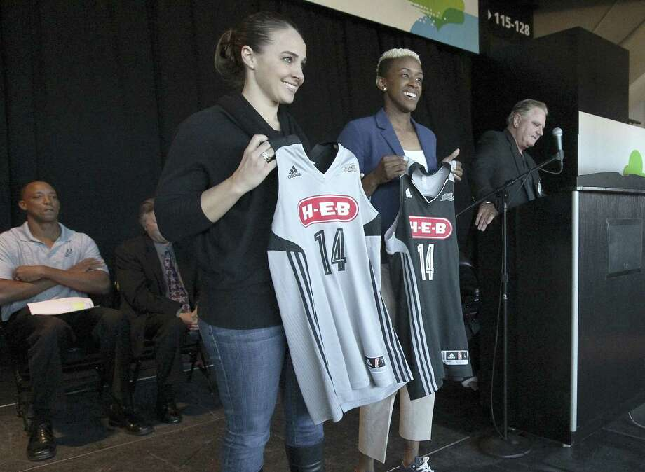 San Antonio Stars players Becky Hammon (left) and Danielle Robinson show off the team's new uniforms with the logo of the H-E-B Grocery Co. Photo: Kin Man Hui / San Antonio Express-News / ©2013 San Antonio Express-News