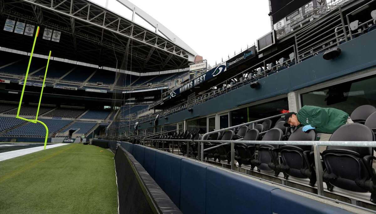 Basilio Valdez, right, cleans off the outdoor seats of field-level suites as he helps prepare CenturyLink Field for the NFL football NFC championship game in Seattle, Tuesday, Jan. 14, 2014. The game will be played between the Seattle Seahawks and the San Francisco 49ers on Sunday.