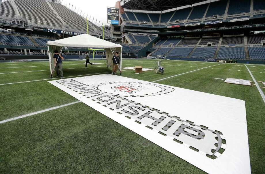 Workers move a portable shelter near a template for an NFL football championship logo Tuesday, Jan. 14, 2014 as they help prepare CenturyLink Field for Sunday's NFL football NFC championship between the Seattle Seahawks and the San Francisco 49ers in Seattle. The shelter will be used to keep rain off the logo paint while it dries. Photo: Ted S. Warren, AP / AP