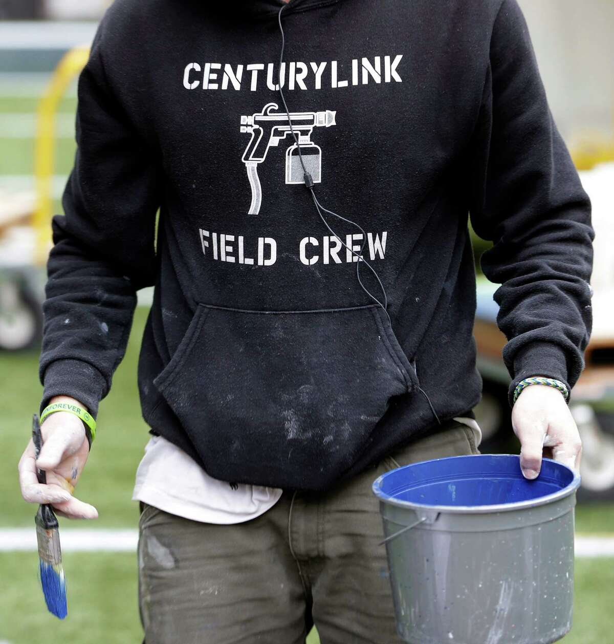 A member of the CenturyLink Field Crew carries a paint bucket as he helps prepare CenturyLink Field for the NFL football NFC championship game in Seattle, Tuesday, Jan. 14, 2014. The game will be played between the Seattle Seahawks and the San Francisco 49ers on Sunday.