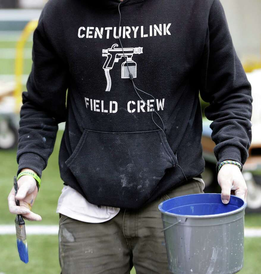 A member of the CenturyLink Field Crew carries a paint bucket as he helps prepare CenturyLink Field for the NFL football NFC championship game in Seattle, Tuesday, Jan. 14, 2014. The game will be played between the Seattle Seahawks and the San Francisco 49ers on Sunday. Photo: Ted S. Warren, AP / AP