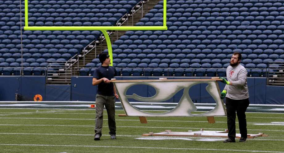 Dalton Niles, left, and Nicholas Clark, right, carry a template for a 20-yard line number as they prepare CenturyLink Field for the NFL football NFC championship game in Seattle, Tuesday, Jan. 14, 2014. The game will be played between the Seattle Seahawks and the San Francisco 49ers on Sunday. Photo: Ted S. Warren, AP / AP