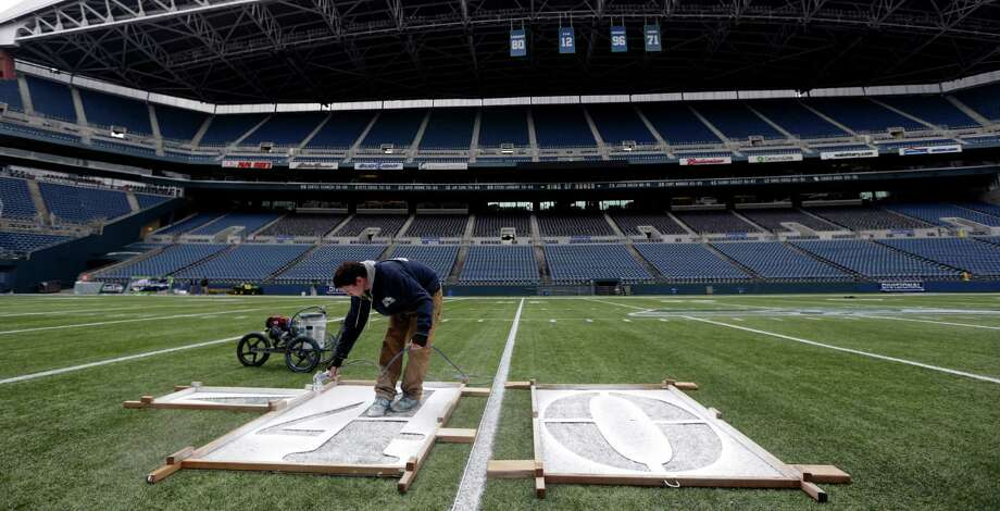 Tim Hardman uses a template to mark the 40-yard line at CenturyLink Field, Tuesday, Jan. 14, 2014, in Seattle. Hardman helped prepare for Sunday's NFL football NFC championship game between the Seattle Seahawks and the San Francisco 49ers . Photo: Ted S. Warren, AP / AP