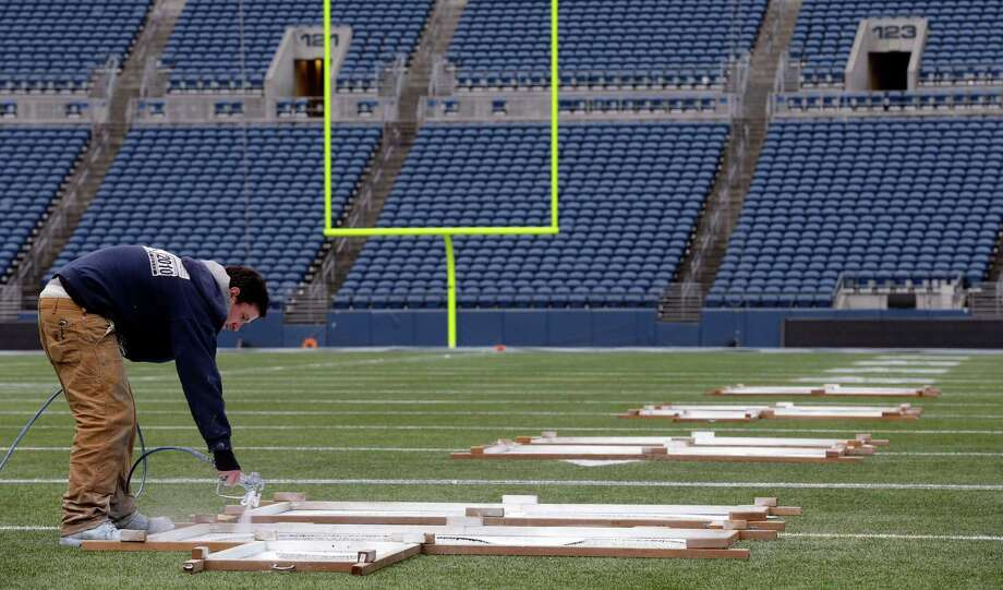 Tim Hardman uses templates to paint yard-line numbers on Tuesday, Jan. 14, 2014, in Seattle. Hardman helped prepare CenturyLink Field for Sunday's NFL football NFC championship game between the Seattle Seahawks and the San Francisco 49ers. Photo: Ted S. Warren, AP / AP
