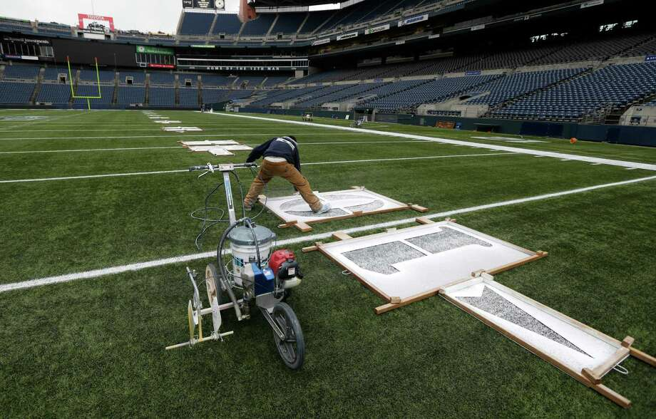 Tim Hardman uses a template to mark the 10-yard-line, Tuesday, Jan. 14, 2014 as he helps prepare CenturyLink Field for Sunday's NFL football NFC Championship between the Seattle Seahawks and the San Francisco 49ers in Seattle. Photo: Ted S. Warren, AP / AP