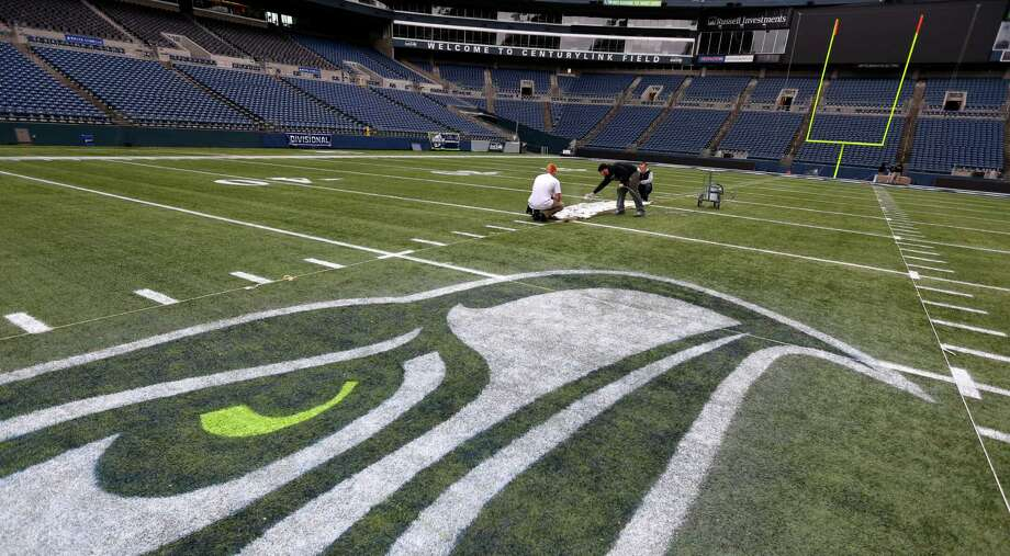 Members of the CenturyLink Field stadium operations team use template to paint hash marks near the Seattle Seahawks logo Tuesday, Jan. 14, 2014 as they prepare the field for Sunday's NFL football NFC championship between the Seattle Seahawks and the San Francisco 49ers in Seattle. Photo: Ted S. Warren, AP / AP
