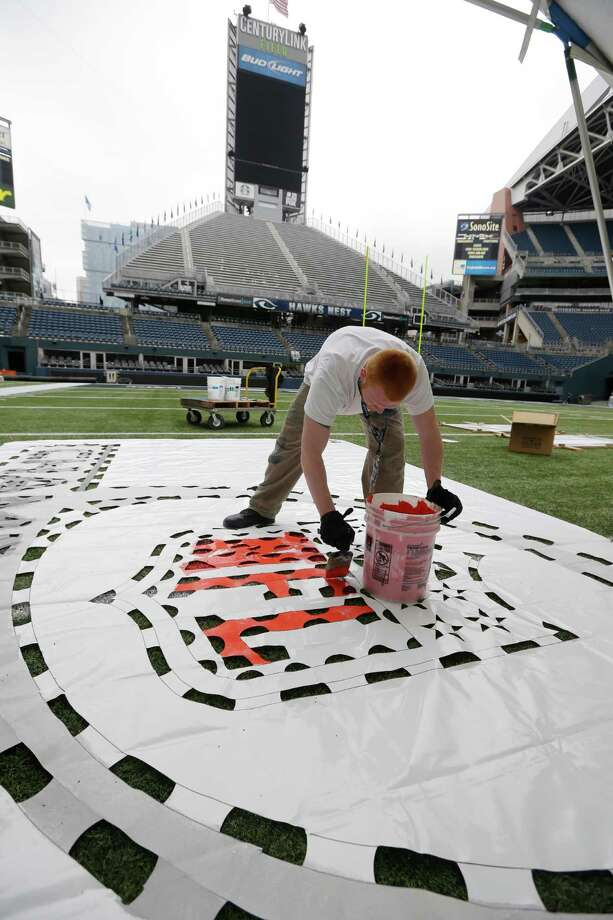Gavin Santjer uses a template to paint an NFL football championship logo Tuesday, Jan. 14, 2014 as he helps prepare CenturyLink Field for Sunday's NFL football NFC championship between the Seattle Seahawks and the San Francisco 49ers in Seattle. Photo: Ted S. Warren, AP / AP