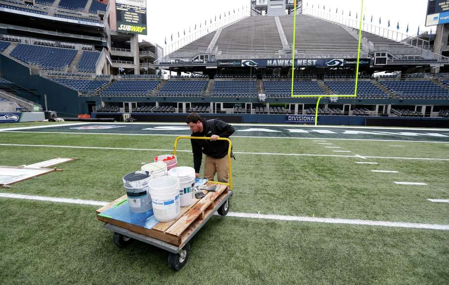 Sam Town, field supervisor at CenturyLink Field, lifts up a cart with paint buckets on it so it won't mar a freshly painted yard-line marker, Tuesday, Jan. 14, 2014 as he works to prepare the field for Sunday's NFL football NFC Championship between the Seattle Seahawks and the San Francisco 49ers in Seattle. Photo: Ted S. Warren, AP / AP