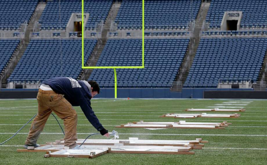 Tim Hardman uses a template to mark the 40-yard-line, Tuesday, Jan. 14, 2014 as he helps prepare CenturyLink Field for Sunday's NFL football NFC Championship between the Seattle Seahawks and the San Francisco 49ers in Seattle. Photo: Ted S. Warren, AP / AP