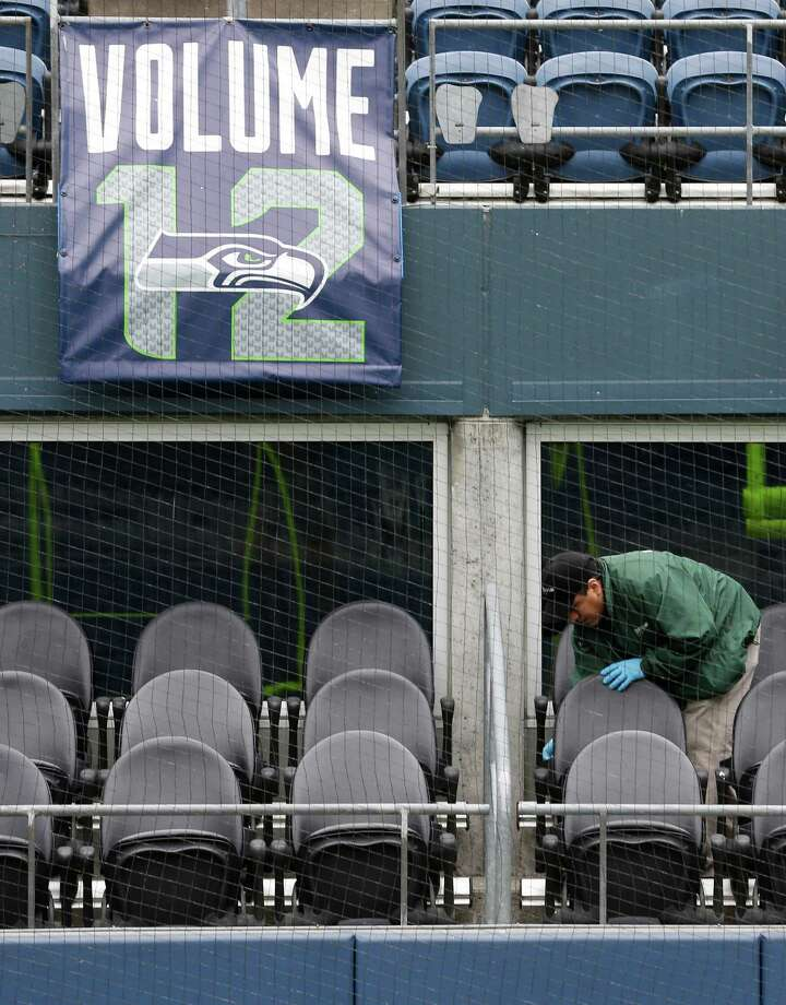 Basilio Valdez, right, cleans off the outdoor seats of field-level suites, Tuesday, Jan. 14, 2014 as he helps prepare CenturyLink Field for Sunday's NFL football NFC championship between the Seattle Seahawks and the San Francisco 49ers in Seattle. Photo: Ted S. Warren, AP / AP
