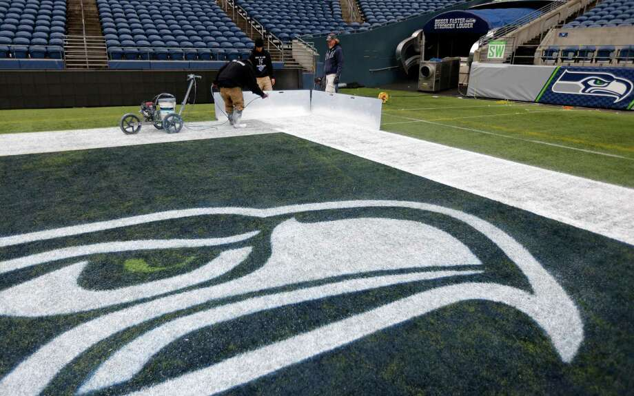 Members of the CenturyLink Field stadium operations team an end zone line near the Seattle Seahawks logo Tuesday, Jan. 14, 2014 as they prepare the field for Sunday's NFL football NFC championship between the Seattle Seahawks and the San Francisco 49ers in Seattle. Photo: Ted S. Warren, AP / AP
