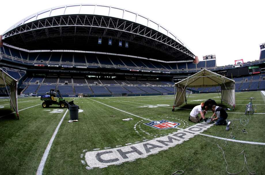 In this photo made with a fisheye wide-angle lens workers paint an NFL championship logo Tuesday, Jan. 14, 2014 as they prepare CenturyLink Field for Sunday's NFL football NFC championship between the Seattle Seahawks and the San Francisco 49ers in Seattle. Photo: Ted S. Warren, AP / AP