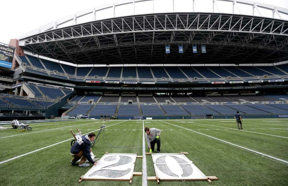Tim Hardman, left, and Nicholas Clark, right, use a template to mark the 20-yard-line, Tuesday, Jan. 14, 2014 as they help prepare CenturyLink Field for Sunday's NFL football NFC Championship between the Seattle Seahawks and the San Francisco 49ers in Seattle. Photo: Ted S. Warren, AP / AP