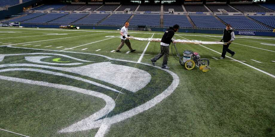 Members of the CenturyLink Field stadium operations team carry a template to paint hash marks near the Seattle Seahawks logo Tuesday, Jan. 14, 2014 as they prepare the field for Sunday's NFL football NFC championship between the Seattle Seahawks and the San Francisco 49ers in Seattle. Photo: Ted S. Warren, AP / AP