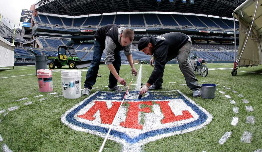In this photo made with a fisheye wide-angle lens, Austin Amon, left, and Ryan Johnson, right, paint an NFL logo Tuesday, Jan. 14, 2014 as they prepare CenturyLink Field for Sunday's NFL football NFC championship between the Seattle Seahawks and the San Francisco 49ers in Seattle. Photo: Ted S. Warren, AP / AP