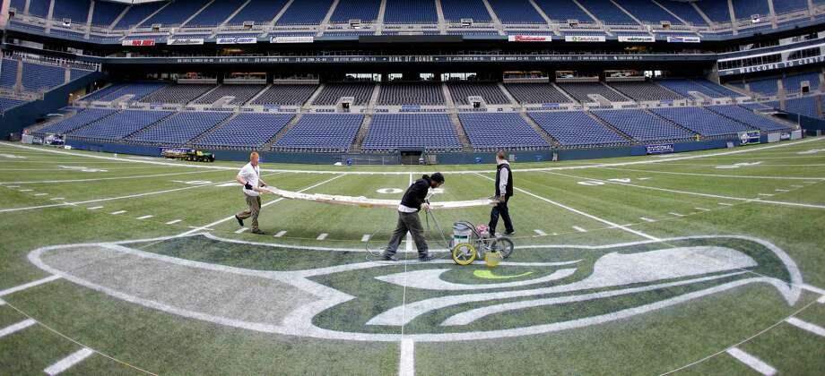Members of the CenturyLink Field stadium operations team carry a template for painting hash marks Tuesday, Jan. 14, 2014 as they prepare the field for Sunday's NFL football NFC championship between the Seattle Seahawks and the San Francisco 49ers in Seattle. Photo: Ted S. Warren, AP / AP