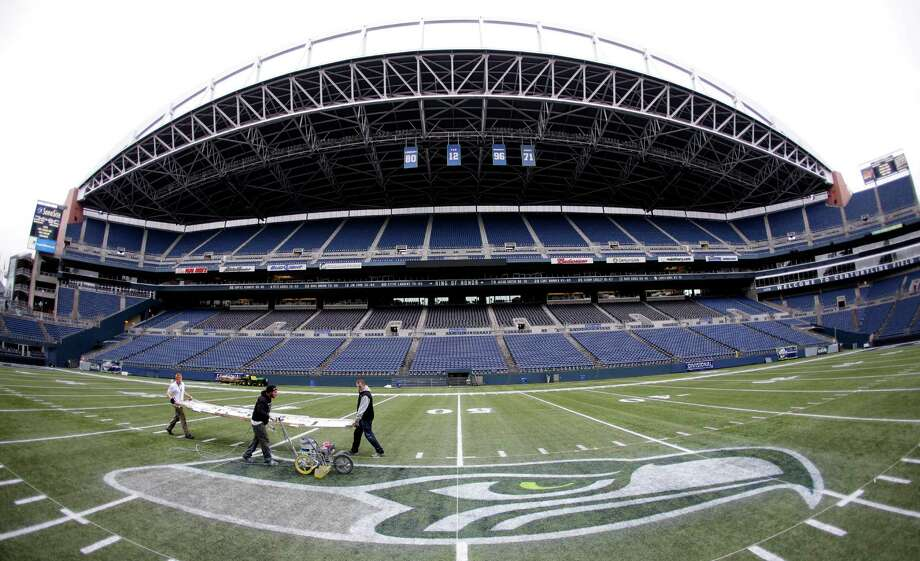 In this photo made with a fisheye lens, members of the CenturyLink Field stadium operations team carry a template for painting hash marks Tuesday, Jan. 14, 2014, as they prepare the field in Seattle for Sunday's NFL football NFC championship between the Seattle Seahawks and the San Francisco 49ers. Photo: Ted S. Warren, AP / AP