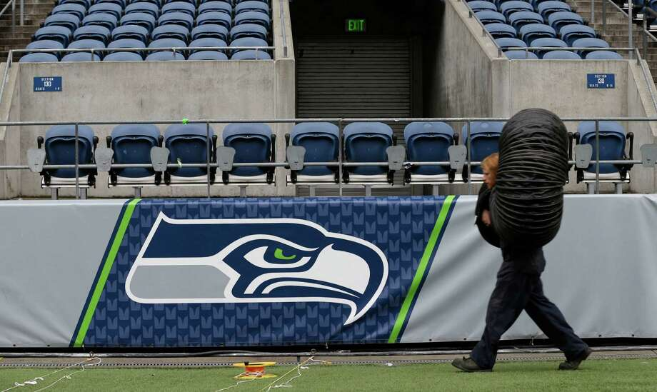 Chris Pearisaeff carries a piece of heater ductwork past the Seattle Seahawks logo as he works Tuesday, Jan. 14, 2014, in Seattle, to help prepare the field for Sunday's NFL football NFC Championship between the Seattle Seahawks and the San Francisco 49ers. (AP Photo/Ted S. Warren Photo: Ted S. Warren, AP / AP