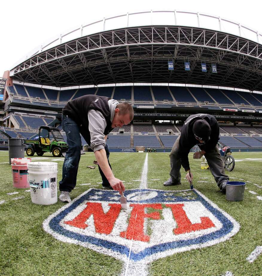 In this photo made with a fisheye lens, Austin Amon, left, and Ryan Johnson, right, paint an NFL championship logo Tuesday, Jan. 14, 2014, in Seattle as they prepare CenturyLink Field for Sunday's NFL football NFC championship game between the Seattle Seahawks and the San Francisco 49ers. Photo: Ted S. Warren, AP / AP