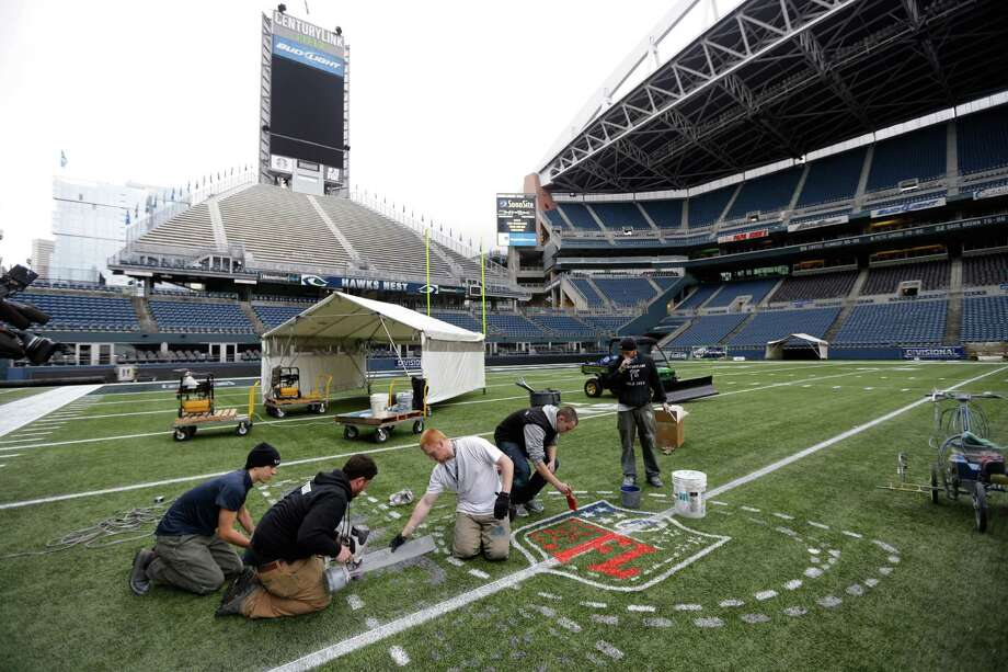 Members of the CenturyLink Field stadium operations team paint an NFL championship logo Tuesday, Jan. 14, 2014 in Seattle as they prepare the field for Sunday's NFL football NFC championship game between the Seattle Seahawks and the San Francisco 49ers. Photo: Ted S. Warren, AP / AP