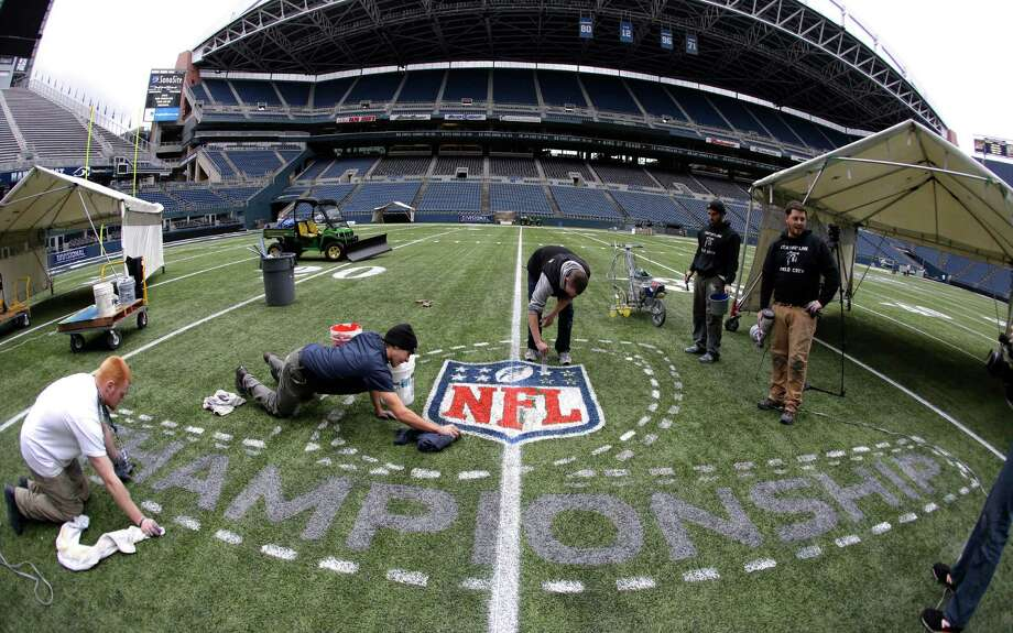 In this photo made with a fisheye lens, members of the CenturyLink Field stadium operations team paint an NFL championship logo Tuesday, Jan. 14, 2014, in Seattle as they prepare the field for Sunday's NFL football NFC championship game between the Seattle Seahawks and the San Francisco 49ers. Photo: Ted S. Warren, AP / AP