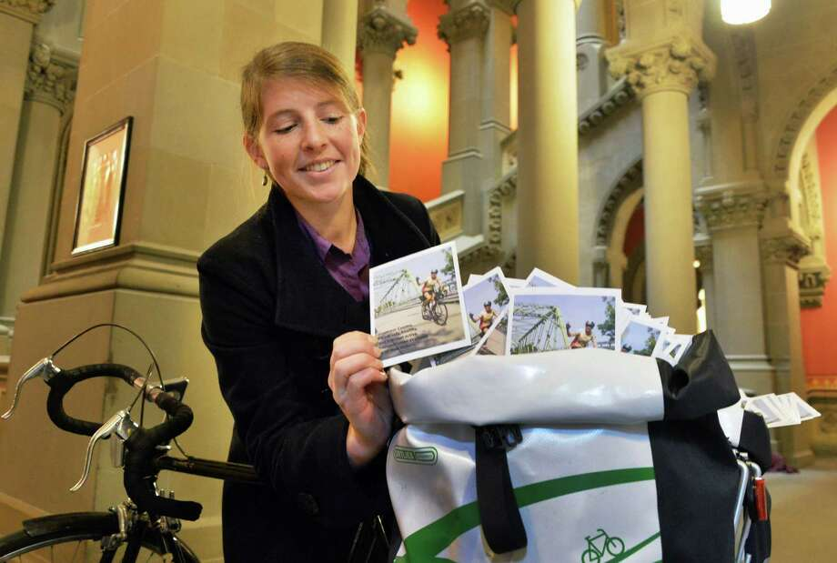 Jackie Mullen of Albany of New Yorkers for Active Transportation with a bicycle saddlebags full of more than 1300 postcards calling for the Gov. to fund pedestrian and bcycling projects inside the State Capitol Tuesday Jan. 14, 2014, in Albany, NY.  (John Carl D'Annibale / Times Union) Photo: John Carl D'Annibale
