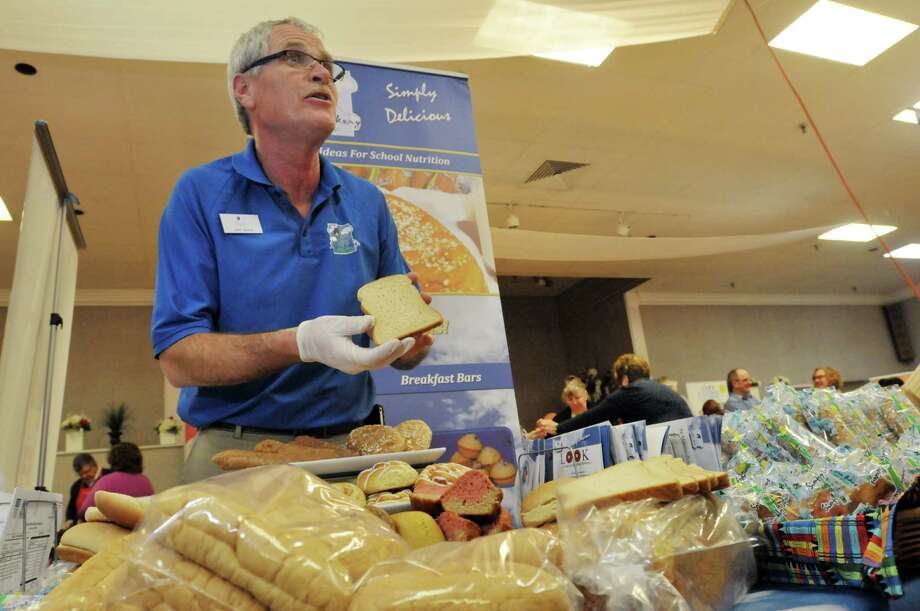 John Eberts, sales director of Sky Blue Bakery, shows off the company's white, 100% whole wheat bread at the New York School Nutrition Association Regional Industry Seminar on Tuesday, Jan. 14, 2014 in Albany, NY.  (Paul Buckowski / Times Union) Photo: Paul Buckowski / 00025358A