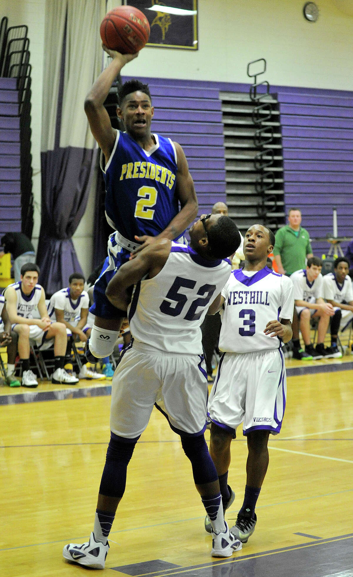 Westhill's Chianta' Holtzclaw takes a charge from Harding's T.J. Killings during their basketball game at Westhill High School in Stamford, Conn., on Tuesday, Jan. 14, 2014. Westhill won, 67-50.