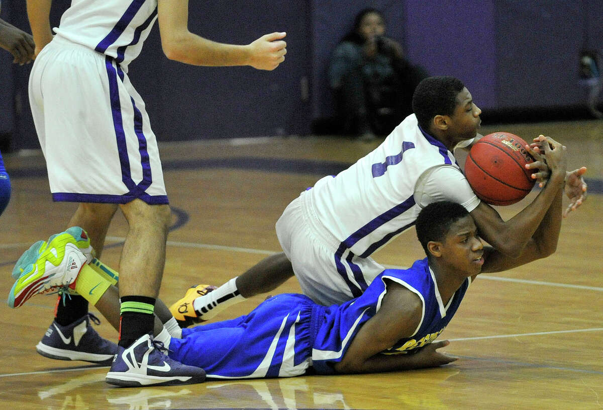 Westhill's Jeremiah Livingston wrestles the ball from Malcolm Simmons immediately after the tipoff during their basketball game at Westhill High School in Stamford, Conn., on Tuesday, Jan. 14, 2014. Westhill won, 67-50.