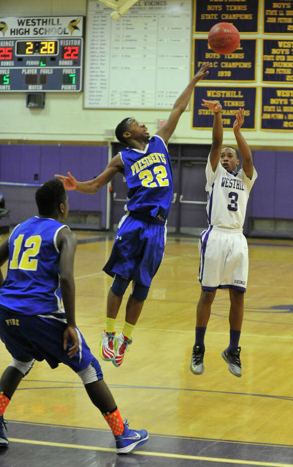 Westhill's C.J. Donaldson attempts a three-pointer with a leaping Malcolm Simmons, of Harding, in his way during their basketball game at Westhill High School in Stamford, Conn., on Tuesday, Jan. 14, 2014. Westhill won, 67-50. Photo: Jason Rearick / Stamford Advocate