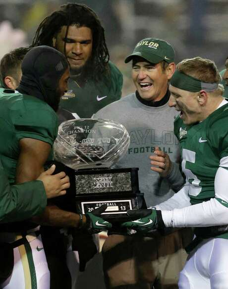 Baylor head coach Art Briles, center right, celebrates with players Ahmad Dixon, left, Cyril Richardson, center left,  and Eddie Lackey (5) with the Big 12 trophy after their NCAA college football game against Texas, Saturday, Dec. 7, 2013, in Waco, Texas. Baylor won 30-10 to clinch the title.  (AP Photo/LM Otero) Photo: LM Otero, STF / AP