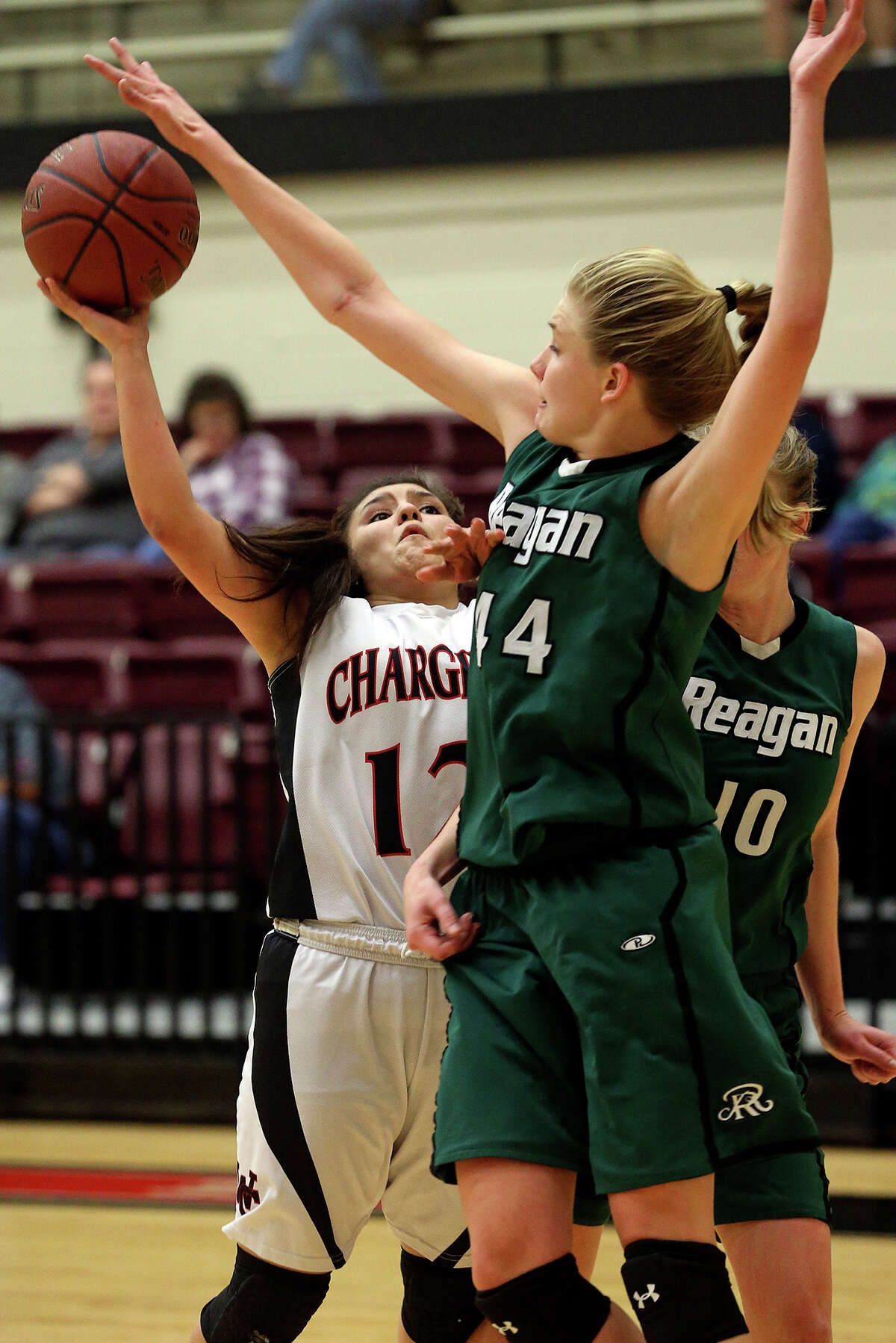 Charger Guard Mikki Flores tries a shot under Rattler center Sara Lewis as Reagan plays Churchill in girls basketball at Littleton Gym on January 14, 2014.