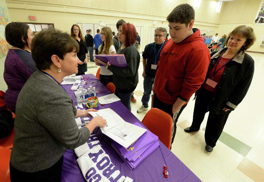 Student Benjamin Roseberger, right,  listens to Mary Grace Tompkins, a teacher at Troy Hi,  as she give her pitch for the benefits of attending Troy High School during High School Fair Day at Gardener-Dickinson Tuesday afternoon Jan. 14, 2014 in Wynantskill, N.Y.  Standing with Benjamin is are his parents Richard Janet Roseberger, right.  Wynantskill, N.Y. Wynantskill doesn?t have a high school of its own, so 8th grade students are offered a choice in which high school to attend come September. (Skip Dickstein / Times Union) Photo: SKIP DICKSTEIN / 0025311A