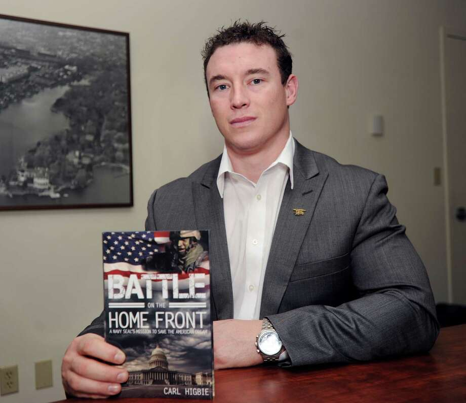 """Holding his book """"Battle on the Home Front,"""" Carl Higbie, a former Navy SEAL who did two tours of duty in Iraq, at the office of the Greenwich Time on Tuesday. Higbie, a Greenwich resident, is running for Congress in the 4th District as a Republican. Photo: Bob Luckey / Greenwich Time"""