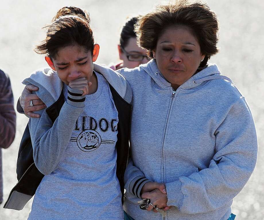 A student, left, is hugged following a shooting at Berrendo Middle School, Tuesday, Jan. 14, 2014, in Roswell, N.M. A shooter opened fire at the middle school, injuring at least two students before being taken into custody. Roswell police said the school was placed on lockdown, and the suspected shooter was arrested. (AP Photo/Roswell Daily Record, Mark Wilson) Photo: Mark Wilson, Associated Press