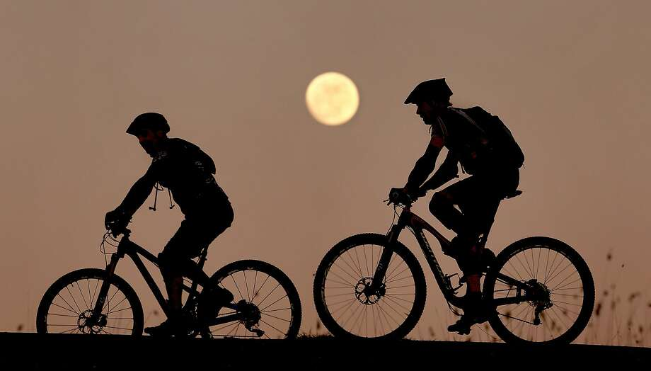 January in Northern California feels a lot like May:Mountain bikers ride over the top of Spring Lake Dam, near Santa Rosa, in record-breaking warm weather. Photo: Kent Porter, Associated Press