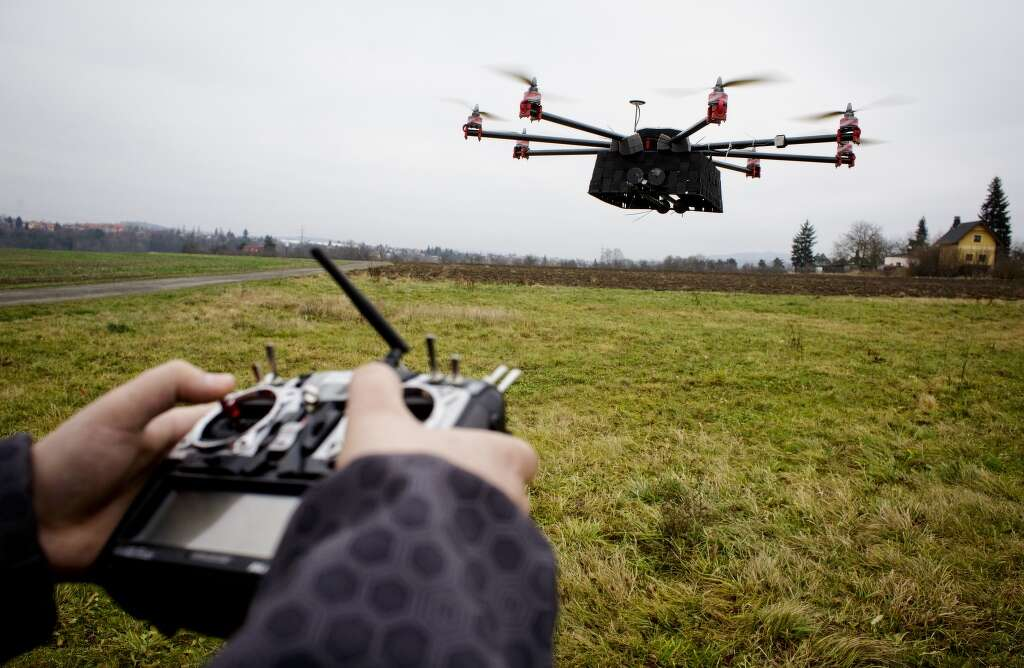A Technician Operates Control Unit To Fly SteadiDrone EI8GHT Octocopter In Field Outside