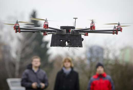 Technicians look on as a SteadiDrone EI8GHT Octocopter hovers during a test flight in a field outside the headquarters of Mensuro Ltd., a distributor for SteadiDrone Ltd. products, in Pilsen, Czech Republic, on Tuesday, Dec. 10, 2013. Photo: Martin Divisek, Bloomberg