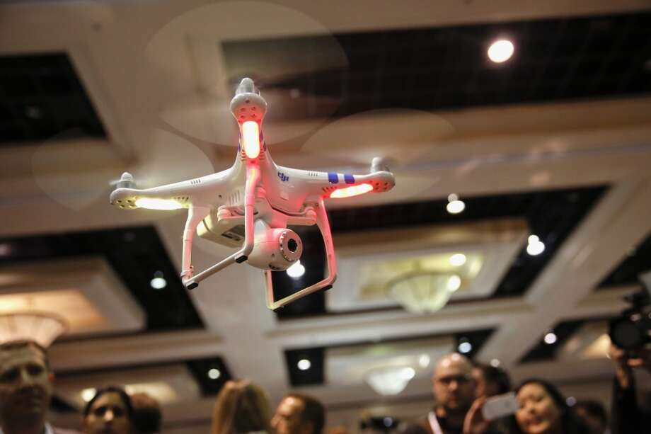 A DJI Innovations Phantom remote-controlled drone hovers above attendees during the CES Unveiled press event prior to the 2014 Consumer Electronics Show in Las Vegas, Nevada, U.S., on Sunday, Jan. 5, 2014. Photo: Patrick T. Fallon, Bloomberg