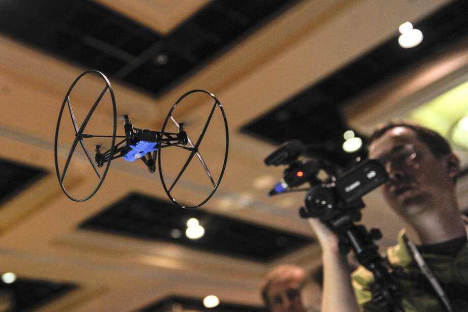 An attendee shoots video of a Parrott Mini Drone during the CES Unveiled press event prior to the 2014 Consumer Electronics Show in Las Vegas, Nevada, U.S., on Sunday, Jan. 5, 2014. Photo: David Paul Morris, Bloomberg