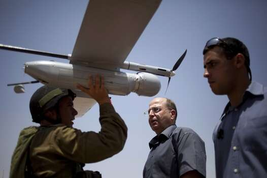 An Israeli soldier holds up a Skylark I (Rochev Shamayim) unmanned drone as part of a demonstration for Israel's Defense Minister Moshe Yaalon, center, in an urban warfare army training facility, near Zeelim, southern Israel. Photo: Ariel Schalit, Associated Press