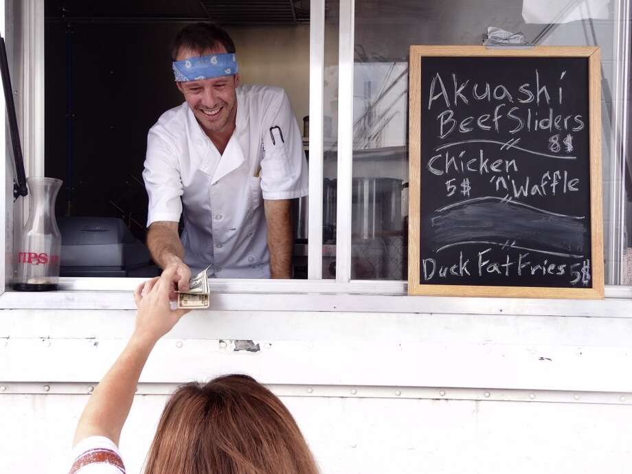 "Jason Paschall, of The Say.She.Ate mobile kitchen, offers ""Mobile Eclectic Fare,"" including Akaushi beef sliders. Saturday, Oct. 8, 2011. Photo: Billy Calzada, Express-News"