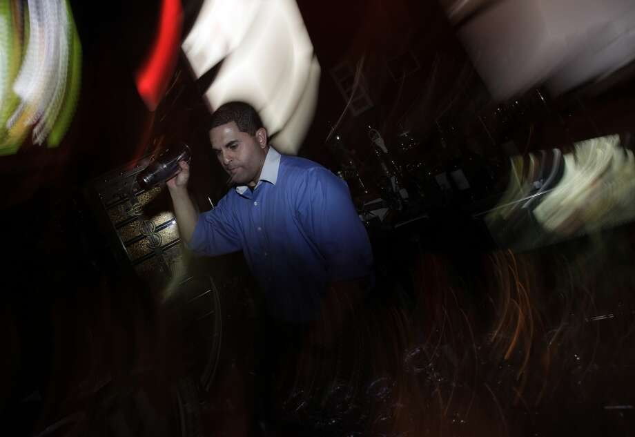 SoHo Wine & Martini Bar manager Eddie Martinez shakes up a martini on Wednesday, June 9, 2010. Photo: Kin Man Hui, Express-News